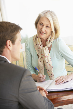 Senior Woman Meeting With Financial Advisor At Home Stock Photo