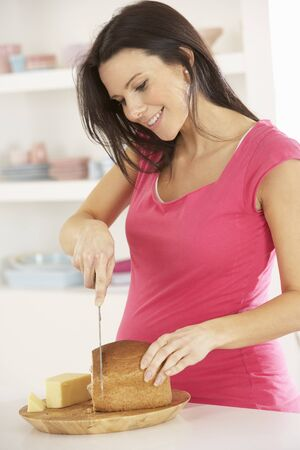 comiendo pan: Mujer embarazada que hace el emparedado en cocina en el hogar