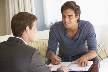financial advisor: Man Meeting With Financial Advisor At Home