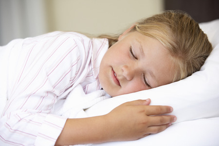 9 year old girl: Young Girl Sleeping In Bed Stock Photo