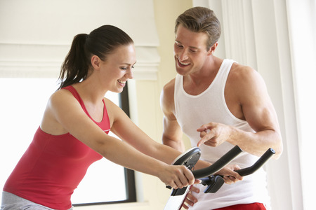 home trainer: Young Couple On Exercise Bike Stock Photo