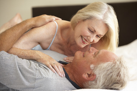 romantic couples: Senior Couple Relaxing On Bed Stock Photo