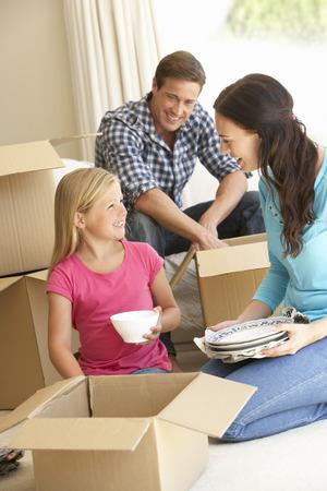 Familie, die in neues Haus umgeben von Verpackungs-Kästen Lizenzfreie Bilder