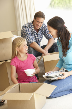 new home: Family Moving Into New Home Surrounded By Packing Boxes