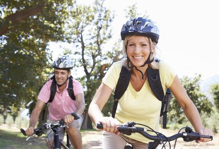 Mittlere gealterte Paare, Radfahren durch Landschaft Standard-Bild