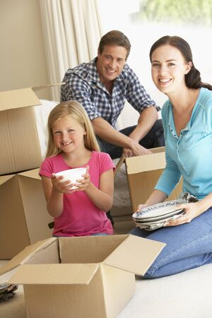 moving in: Family Moving Into New Home Surrounded By Packing Boxes