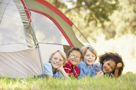 Group Of Boys Having Fun In Tent In Countryside