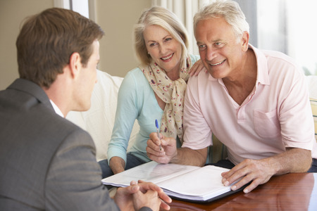financial advice: Senior Couple Meeting With Financial Advisor At Home