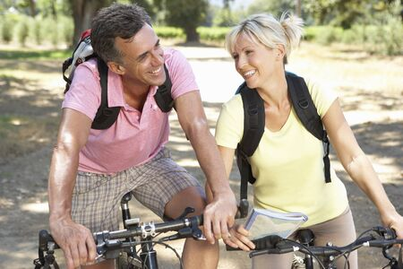 mid age: Middle Aged Couple Cycling Through Countryside