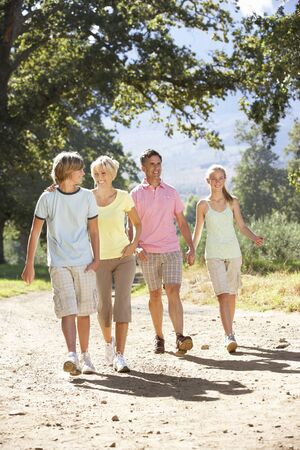 healthy path: Middle Aged Family Walking Through Countryside Stock Photo