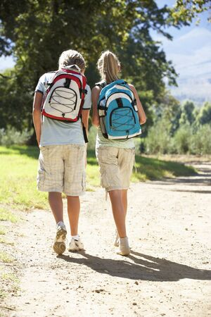 countryside loving: Teenage Couple Hiking Through Countryside Viewed From Back