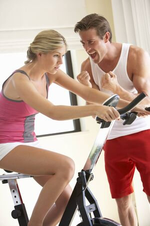 personal trainer: Young Woman On Exercise Bike With Trainer