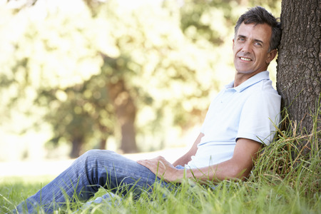 aged: Middle Aged Man Relaxing In Countryside Leaning Against Tree Stock Photo