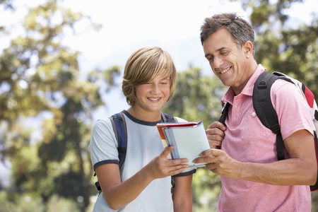 mid teens: Father And Son Hiking Through Countryside Stock Photo