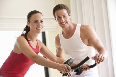 couple exercising: Young Couple On Exercise Bike Stock Photo