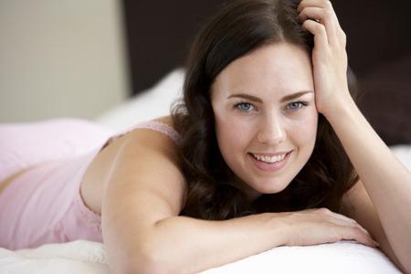 femme brune sexy: Relaxante sur lit de jeune femme