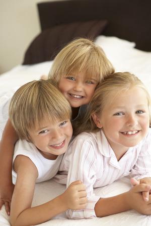 niños riendose: Grupo de niños que se relaja en cama