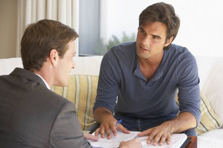 Man Meeting Met Financieel Adviseur At Home Stockfoto