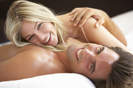 femme amoureuse: Jeune couple relaxant le lit  Banque d'images