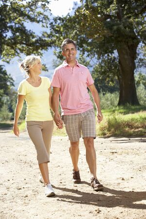 couples outdoors: Middle Aged Couple Walking Through Countryside Stock Photo