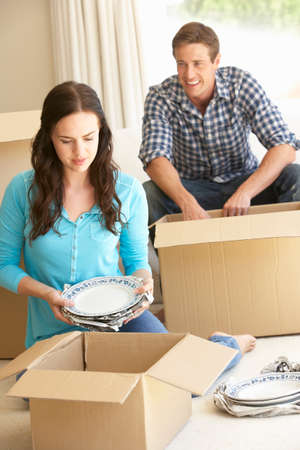 unpacking: Young Couple Moving Into New Home Unpacking Boxes
