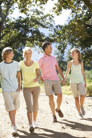 family outside: Middle Aged Family Walking Through Countryside Stock Photo