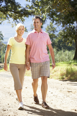 middle aged couple: Middle Aged Couple Walking Through Countryside Stock Photo