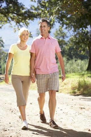 parejas caminando: Pares envejecidos medios que recorren a través de Campo
