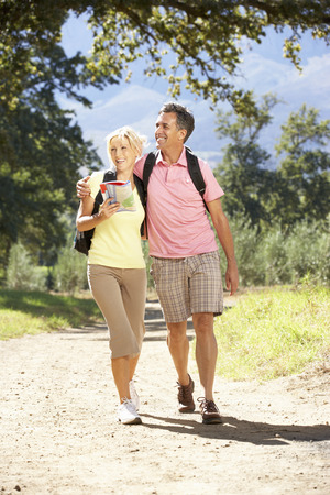Middle Aged Couple Hiking Through Countryside photo