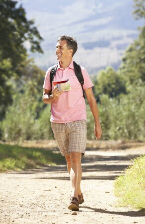 middle aged man: Middle Aged Man Hiking Through Countryside Stock Photo