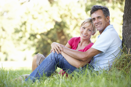 older couples: Middle Aged Couple Relaxing In Countryside Leaning Against Tree Stock Photo
