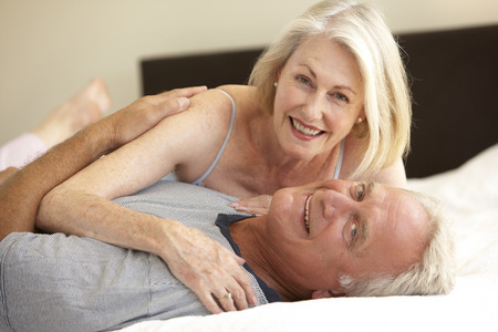 sexy couple in bed: Senior Couple Relaxing On Bed Stock Photo