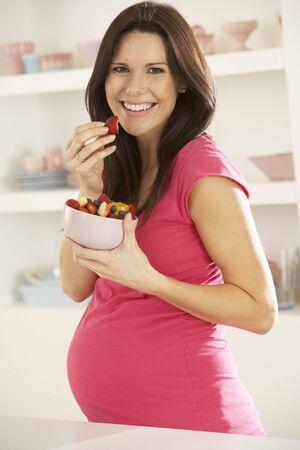 ensalada de frutas: Embarazada ensalada Mujer que come la fruta en la cocina en el hogar Foto de archivo