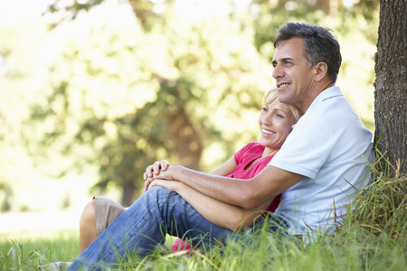 Middle Aged Couple Relaxing In Countryside Leaning Against Tree photo