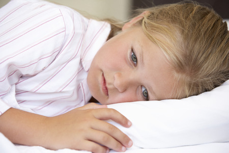 9 year old: Worried Looking Young Girl In Bed Stock Photo