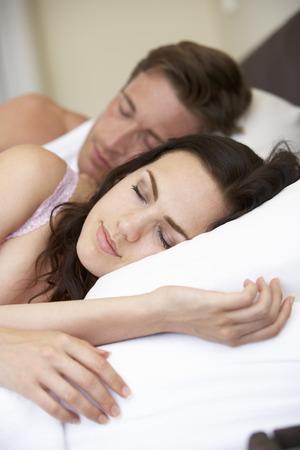 pareja en la cama: Pareja joven que duerme en cama