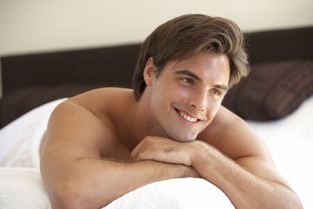 Jeune homme relaxant le lit