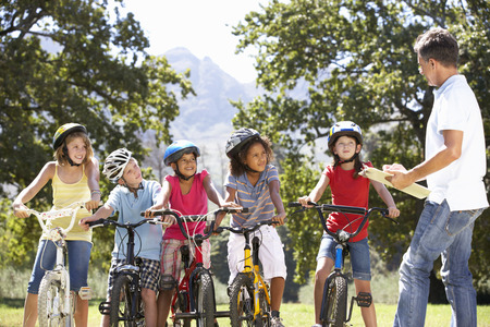 riding helmet: Group Of Children Having Safety Lesson From Adult Whilst Riding Bikes In Countryside