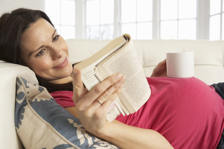 embarazada feliz: Mujer embarazada que bebe la bebida caliente y libro de lectura en el hogar