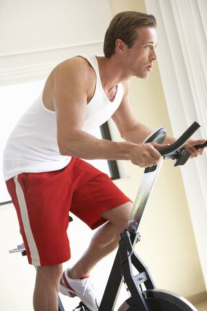 working at home: Young Man On Exercise Bike