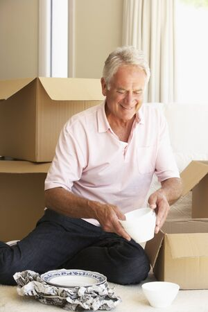 packing boxes: Senior Man Moving Home And Packing Boxes