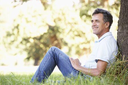 relajado: Hombre envejecido medio que se relaja en campo que se inclina contra árbol