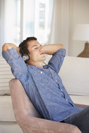 relajado: Hombre joven que se relaja escuchando música en casa