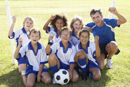 soccer coach: Group Of Children In Soccer Team Celebrating With Trophy Stock Photo