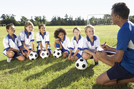 Gruppo di bambini nella squadra di calcio hanno iniziato la formazione con l'allenatore Archivio Fotografico - 41493572