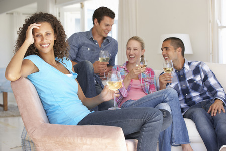 socializing: Group Of Friends Relaxing On Sofa Drinking Wine At Home Together