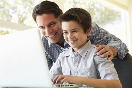 Hispanic Father And Son Using Laptop Banque d'images