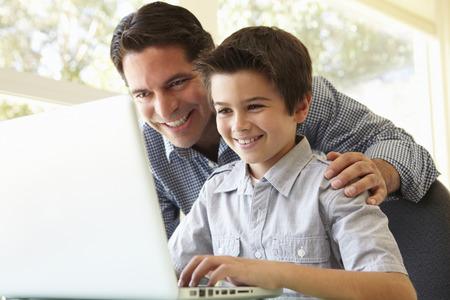 tarea escolar: Padre e hijo hispánicos Usar el portátil