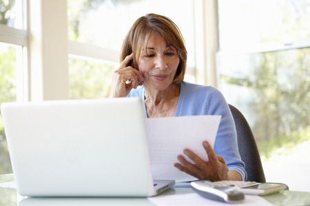 Senior Hispanic Woman Working In Home Office Stock Photo