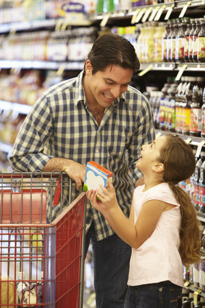 Father and daughter shopping in supermarket photo